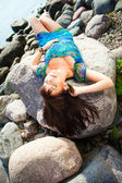 Beautiful brunette girl lying on beach stones — Stock Photo