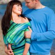 Loving couple embracing on coast of blue sea — Stock Photo