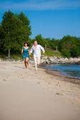 Enamored couple running along the coast of sea — Foto de Stock