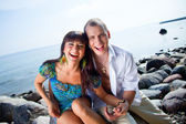Laughing couple near of blue sea — Stock Photo