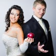 Bride offering a red apple to doubting groom — Stock Photo