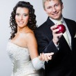 Groom taking red apple from young beautiful bride — Stock Photo