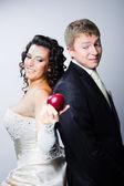Sposa offre una mela rossa a dubitare sposo — Foto Stock