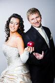 Recién casados novia tentador novio sonriente por manzana roja — Foto de Stock