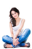 Pretty woman in blue jeans sitting on white floor — Stock Photo