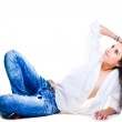Sexy woman in blue jeans lying on white floor — Stock Photo #7365671