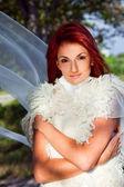Belle femme en blanc contre le ciel bleu et le vert des arbres — Photo