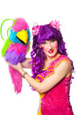 Female clown with colorful toy bird — Stock Photo