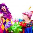 Loving clowns with colorful flowers — Stock Photo