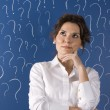 Thinking business woman in front of question marks written blackboard  — Stock Photo
