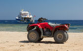 Red quad bike in the desert — Stock Photo