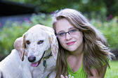 Beautiful blond teenager hugging white dog outdoors — Stock Photo