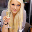 Young woman lifting a glass of champagne — Stock Photo