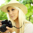 Smiling female with a camera — Stock Photo