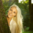Natural beauty hiding behind a tree — Stock Photo