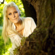 Pretty woman hiding behind tree - Stockfoto