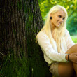 Cute natural beauty relaxing against a tree — Stock Photo