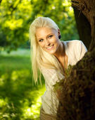 Cute female hiding behind a tree — Stock Photo