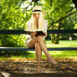 Beauty sitting on a bench reading in the sun — Stock Photo