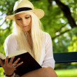 Royalty-Free Stock Photo: Beautiful young woman reading book in a park