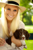 Smiling female holding her puppy. — Stock Photo