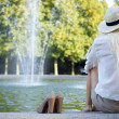 Woman sitting at fountain and waiting - Stock Photo