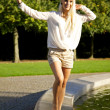 Cute woman balancing on fountain wall - Stock Photo