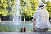 Vrouw zitten bij fontein en wachten — Stockfoto