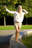 Cute woman balancing on fountain wall — Stock Photo