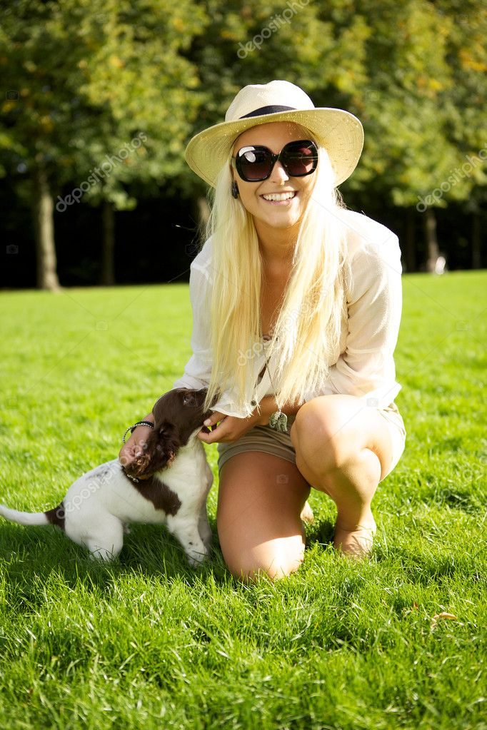 A vivacious sexy young blonde woman in hat and sunglasses relaxes with her puppy in the park. — Stock Photo #7346074