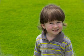 Little boy smiling on green grass — Stock Photo