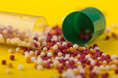 Contents (pills) of capsules scattered on the table — Stock Photo