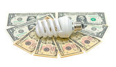 Energy saving light bulb and banknotes on a white background — Stock Photo