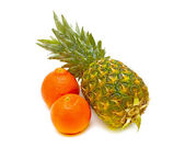 Pineapple and tangerines on a white background — Stock Photo