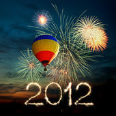 New year 2012 fireworks and hot air balloon at sunset — Stock Photo