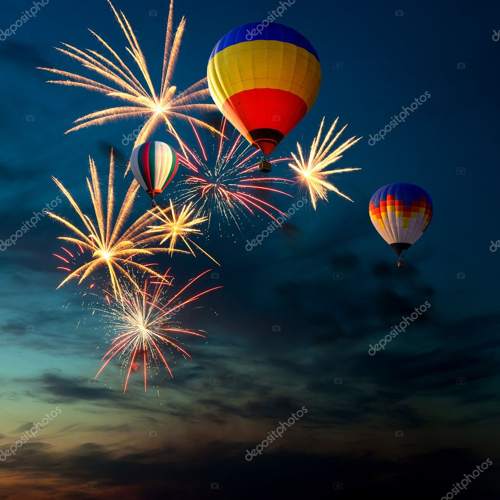 Bright colorful fireworks and hot air-balloon of various colors in the night sky at sunset  Stock Photo #7619517