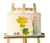 Toile, peintures, un vase avec des brosses et des feuilles sur un chevalet — Photo
