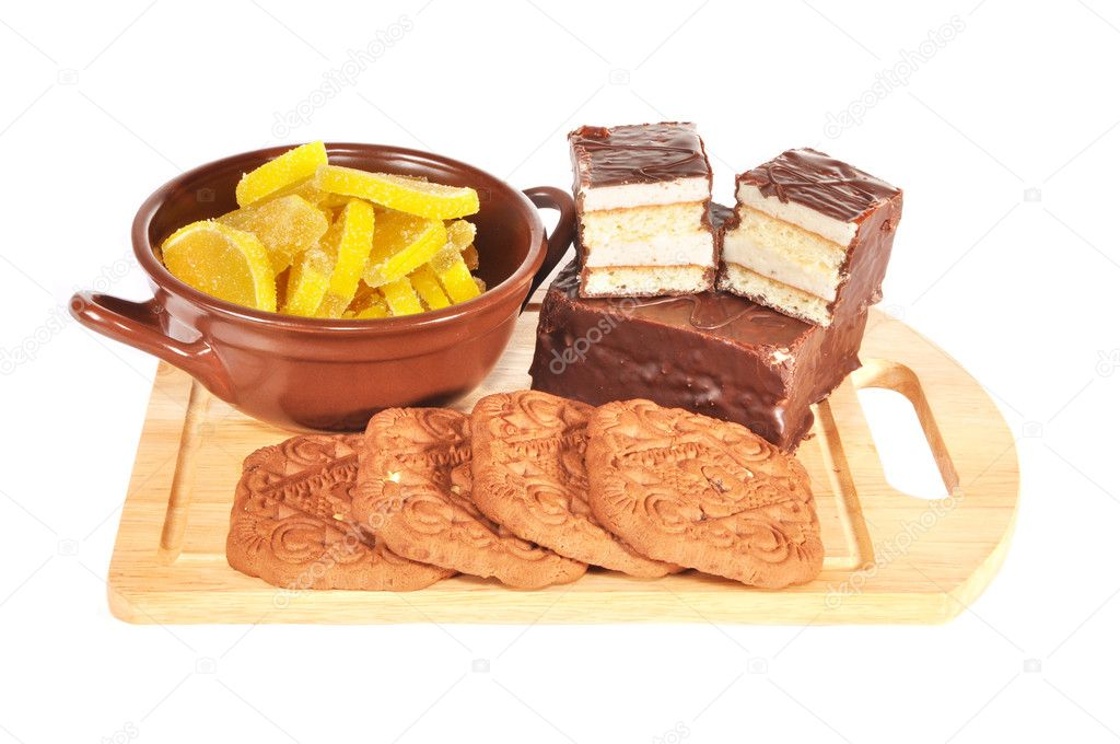Fruit candy, cake, cookies lie on a wooden board — Stock Photo #7249445