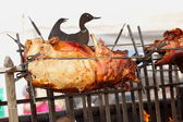 Pig on a spit. Spit roasting is a traditional international method of cooki — Stock Photo