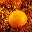 Orange close up on a background of twinkling garlands — Photo