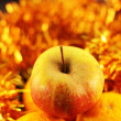 Foto Stock: Apple close-up on background of twinkling garlands