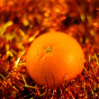 Orange close up on a background of twinkling garlands — Zdjęcie stockowe