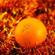 Foto Stock: Orange close up on background of twinkling garlands