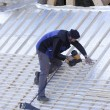 Roofer working on a new roof in wood - Stock Photo