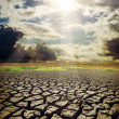 Stock Photo: Dry lake and dramatic sky with sun