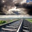 View to railroad goes to horizon under cloudy sky with sun - Stock Photo