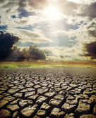Dry lake and dramatic sky with sun — Stockfoto