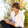 Young Man sitting in a bench with a laptop computer, autumn — Stock Photo #6967735