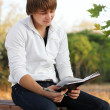 Young relaxed man reading book in nature, autumn — Stock Photo #6967744