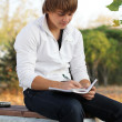 Stock Photo: Young mwrite poetry, autumn outdoors